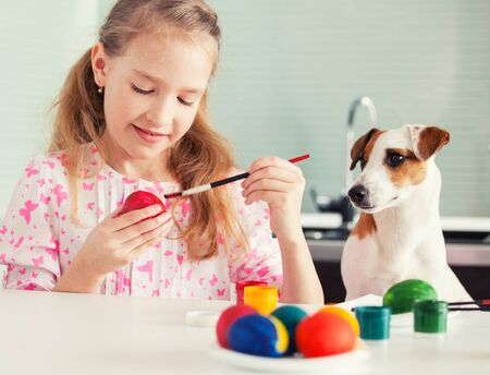 multi age: Easter. Child with dog painting eggs
