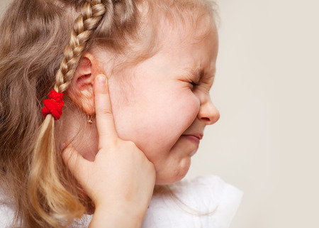 Child has a sore ear. Little girl suffering from otitis