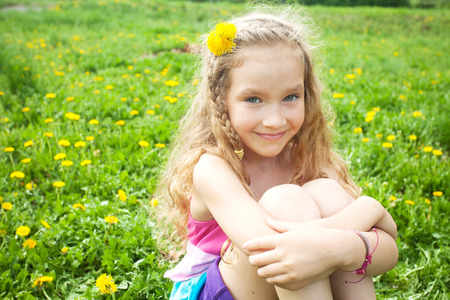 Child at summer. Happy girl outdoors on green grass Stock Photo