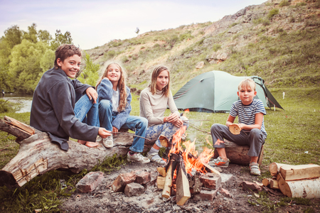 Children in the camp by the fire. Group teen outdoors at summer