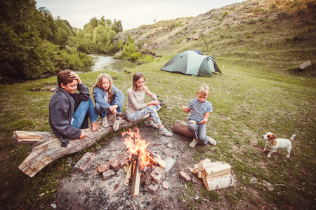 Children in the camp by the bonfire. Group teen outdoors at summer Stock Photo