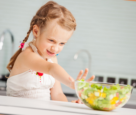 disgusted: Little girl refuses to eat salad. Child looks with disgust for food Stock Photo