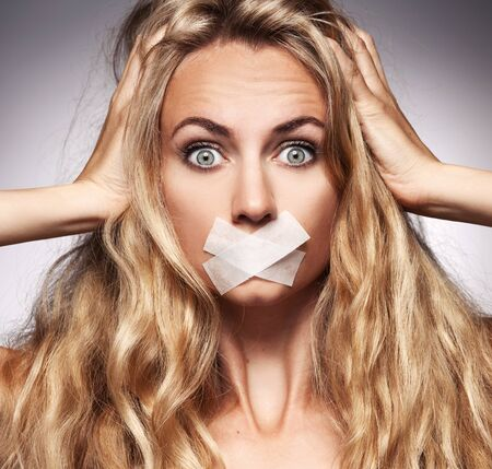 Woman with mouth sealed plaster. Fear, silence, violence