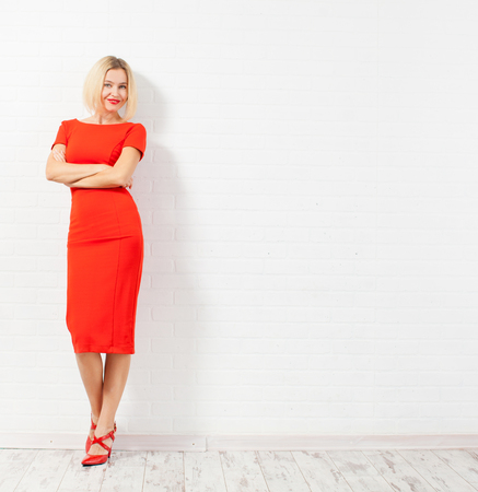 Beautiful happy woman in red dress. Female against a white wall photo