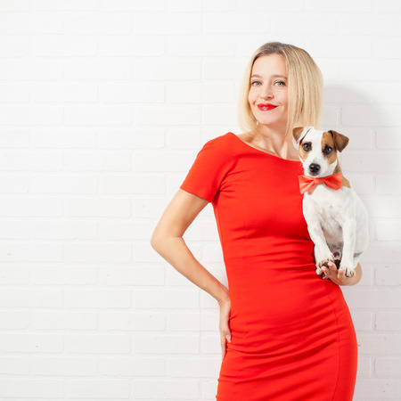 Beautiful happy woman in red dress with dog. Female against a white wall photo
