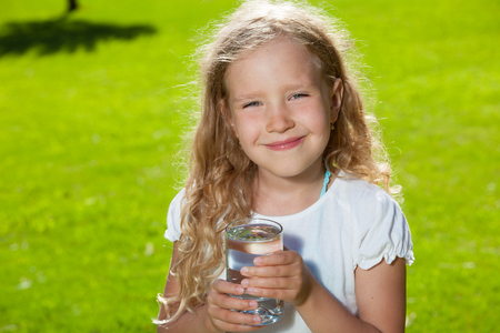 Child drinking water. Girl outdoors Stock Photo