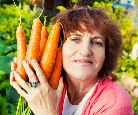 cultivating: Woman grows harvest in the garden. Senior with carrot