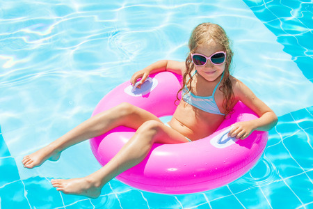 Girl on inflatable ring in swimming pool. Vacations Stock Photo