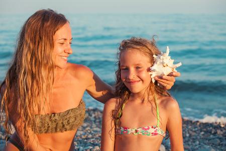 Kind en moeder op zee achtergrond. Zomervakantie. Familie Stockfoto