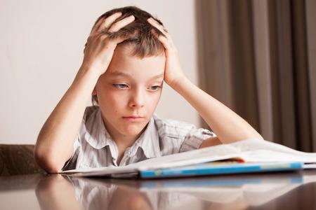 learning by doing: Sad boy doing homework. Child education