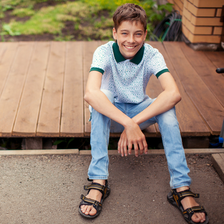 Smiling teen outdoors at summer. Happy one boy 스톡 콘텐츠