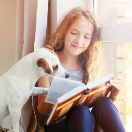 Child with dog reading book at home. Girl with pet sitting at window at read Stockfoto