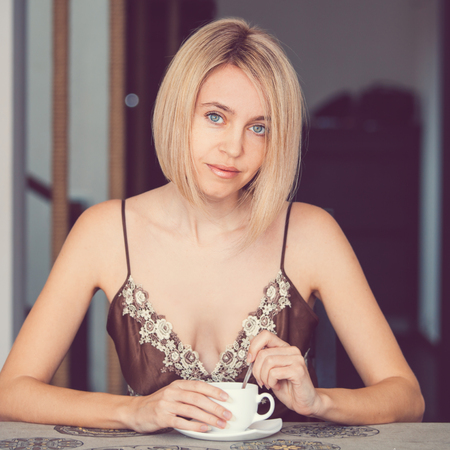 Female in a home clothes drinking coffee. Woman in nightie morning photo