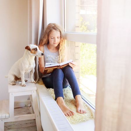 Child reading book at home. Girl sitting at window at read Stock Photo