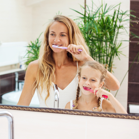 Mother and daughter brushing their teeth in the bathroom. Family at the morning photo