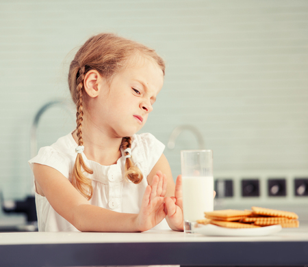 Child looks with disgust for food. Little girl does not like milk