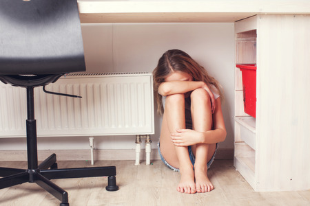 Sad child at home. Abuse. Depression girl indoors photo