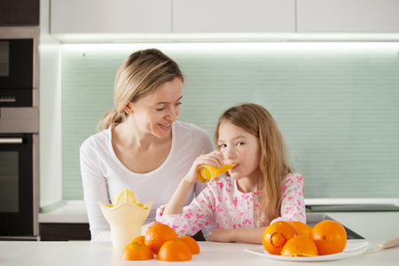 Mother and daughter make orange juice on a juicer photo