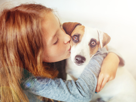 Happy child with dog. Portrait girl with pet. Teen kiss Jack Rassell photo