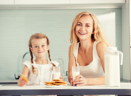 Child with mother drinking milk. Happy family eating at home photo