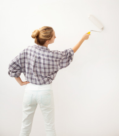 Woman doing repairs. Female paints the wallpaper roll Stock Photo