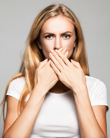 rudeness: Woman with closed mouth. Female covers her mouth with her hands. Silence, fear, violence. Stock Photo