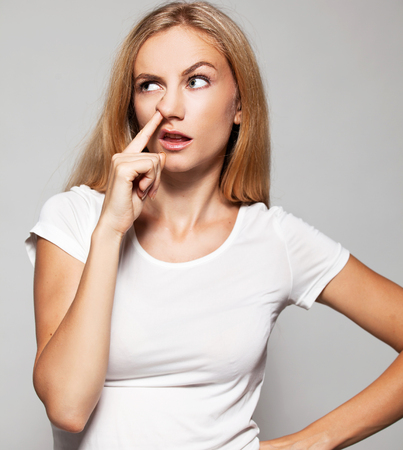 rudeness: Woman picks his nose finger. Female climbs a finger in nose. Embarrassment