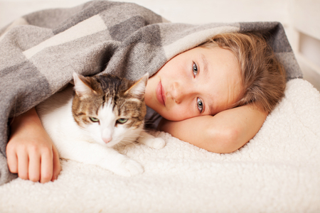 Unhealthy child lying in bed. Sad teen Stock Photo