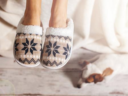Weibliche Beine in den Pantoffeln vor dem hintergrund eines Bretterbodens. Gemütliche, warme und bequeme Hausschuhe an den Füßen