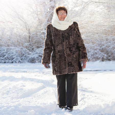 Old woman walking at winter park. Senior outdoors Stock Photo