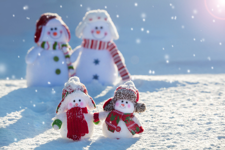 Family snowmans on snow. Mother, father and children at winter