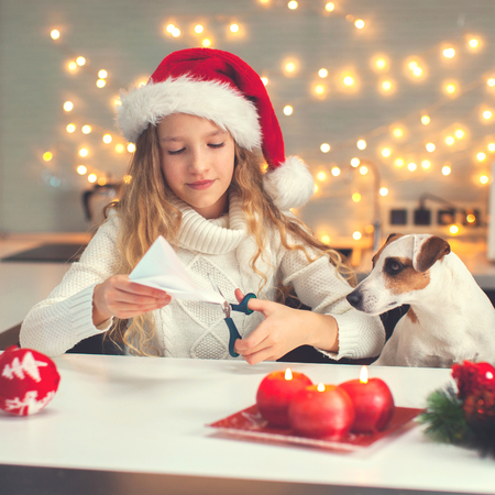 Child carves a snowflake for christmas. Girl is making decoration for the new year Stock Photo