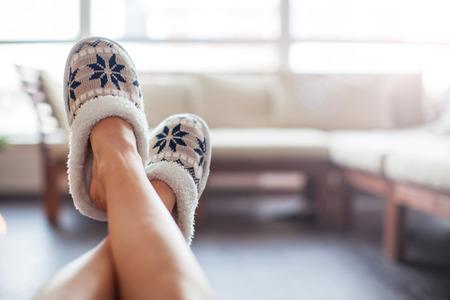 Slippers on women's legs. Soft comfortable home slipper 写真素材