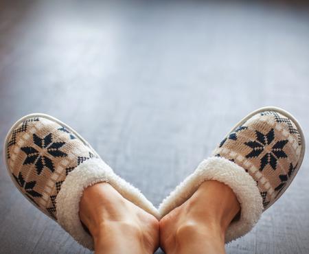 Slippers on women's legs. Soft comfortable home slipper Standard-Bild