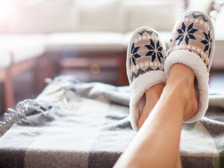 Slippers on women's legs. Soft comfortable home slipper Banque d'images