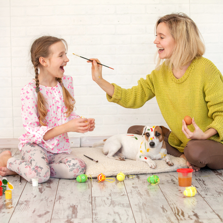 Mom and child decorate Easter eggs. Family at home. Woman with girl painting Stock Photo