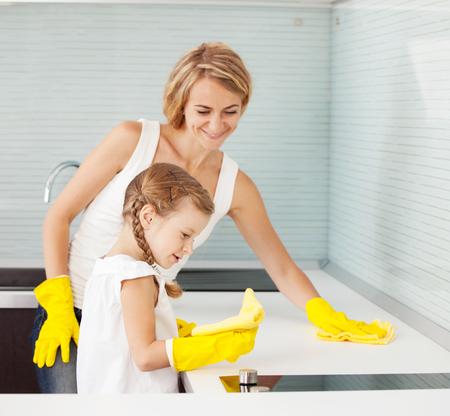 Madre con niño lavando la cocina. Mujer con cocina de limpieza chica Foto de archivo - 96591545