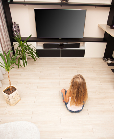 Child watching TV at home. Girl looking at television Archivio Fotografico - 97575297