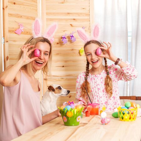 Happy woman and child with easter eggs. Family in an Easter suit with rabbit ears