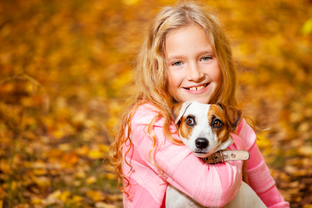 Girl with dog outdoors. Child with pet at autumn