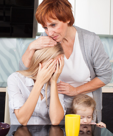 Mother soothes sad daughter. Mature woman calm young woman Фото со стока