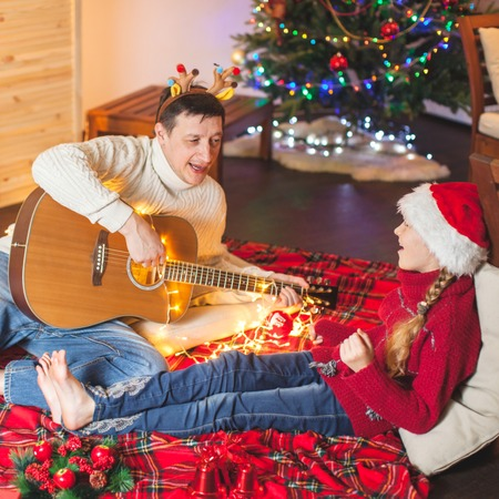 Child with a dad playing the guitar and singing near christmas tree. Happy family near christmas tree. New Year Stock Photo
