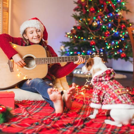 Cild with a dog playing the guitar and singing near christmas tree . Merry christmas and happy New year!