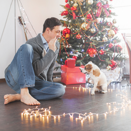 Man with dog near christmas tree
