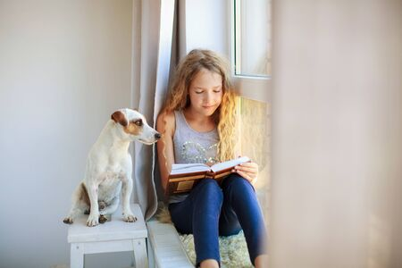 Girl reading book at home Standard-Bild