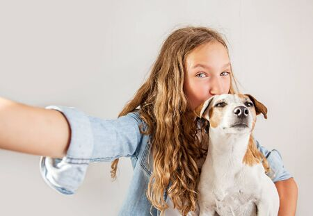 Smiling teen with dog making selfie photo on smartphone over white background  cute girl Stockfoto