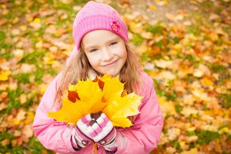 Girl at autumn. Little child outdoors