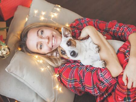 Happy woman with dog on Christmas tree background. Female at home Stock Photo