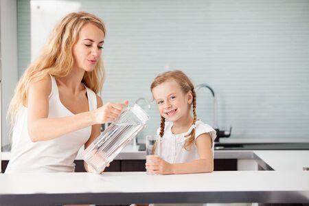Kind met moeder drinkwater uit glas. Gelukkige familie thuis in de keuken Stockfoto