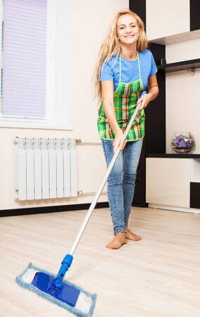 Mujer limpiando el piso en casa. Joven quehaceres domésticos